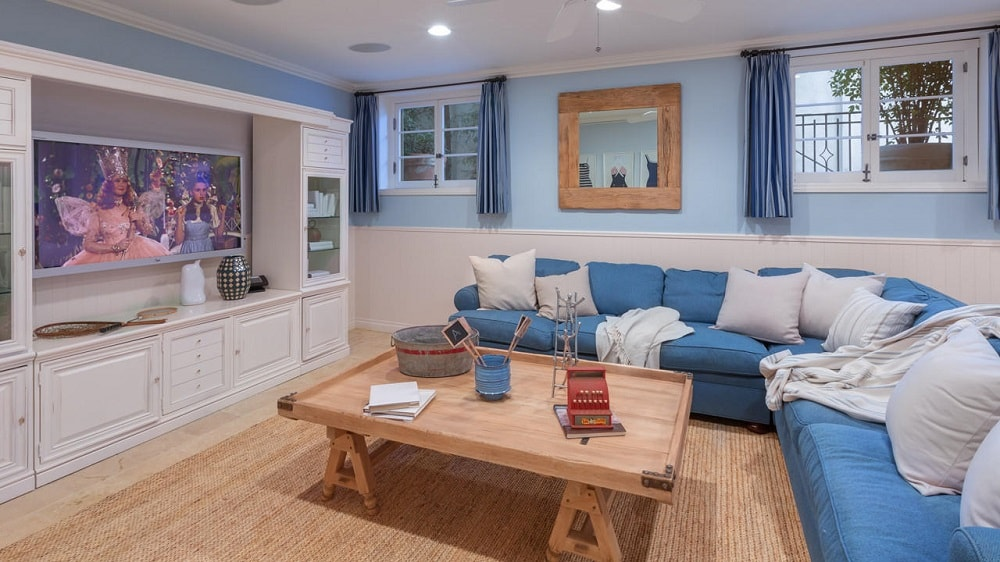The family room has a large blue L-shaped sectional sofa paired with a wooden coffee table across from the large beige wooden structure that houses the TV. Image courtesy of Toptenrealestatedeals.com.