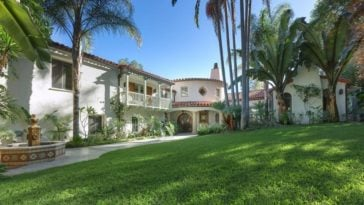 This is a front view of the Spanish Colonial-style home with white exterior walls, terracotta roofs and balconies. These are then complemented by the landscaping that has tall tropical trees, grass lawns and shrubs at the side of the house. Image courtesy of Toptenrealestatedeals.com.