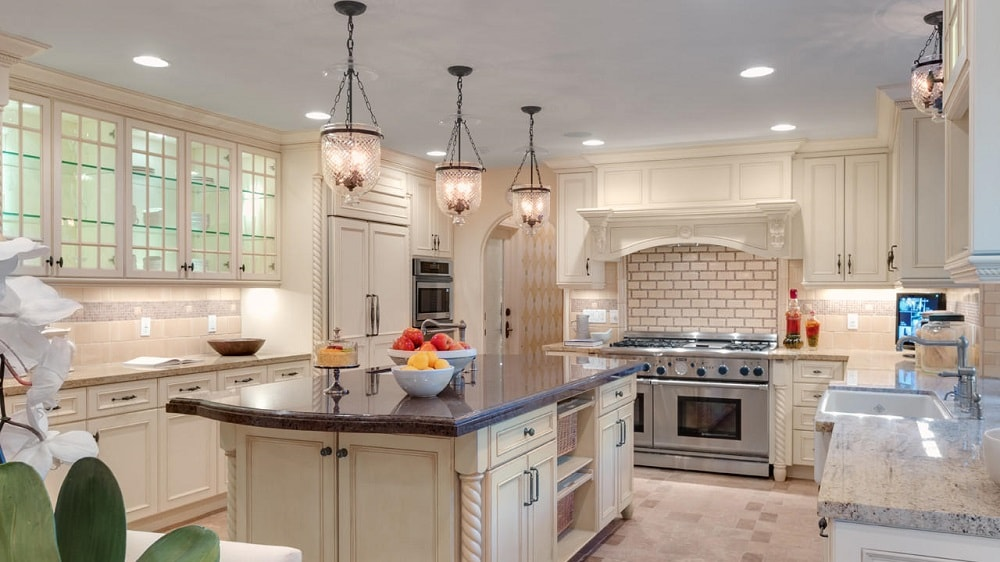 This kitchen has a consistent beige hue to its cabinetry and the large kitchen island contrasted by the black granite countertop. This is then topped with pendant lights. Image courtesy of Toptenrealestatedeals.com.
