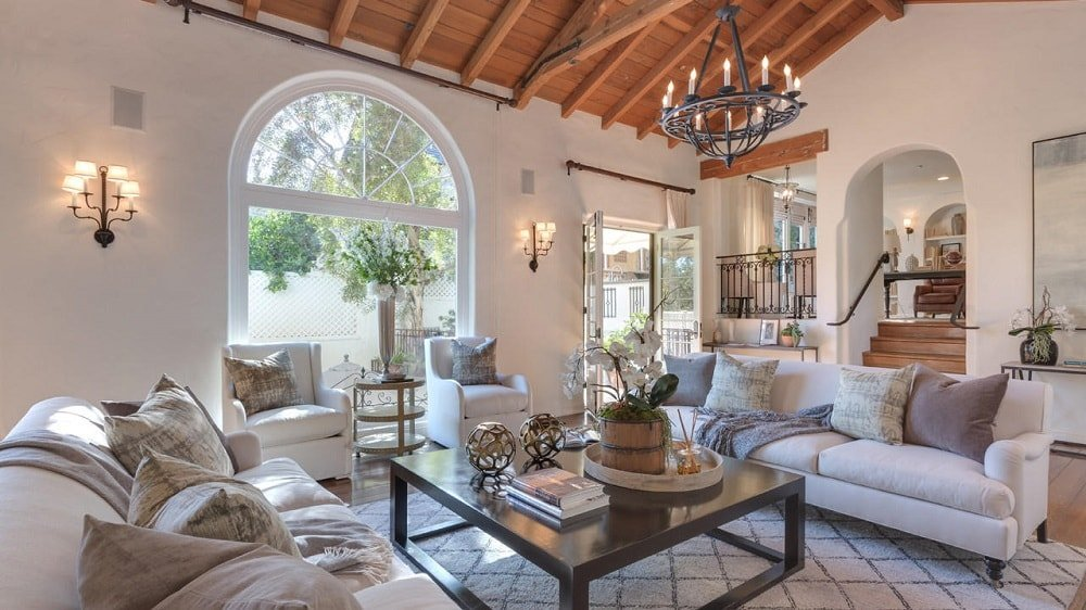 This other look at the living room showcases the large arched entryway that leads to the outdoor areas. This also brings in an abundance of natural lighting for the beige walls and tall wooden ceiling. Image courtesy of Toptenrealestatedeals.com.