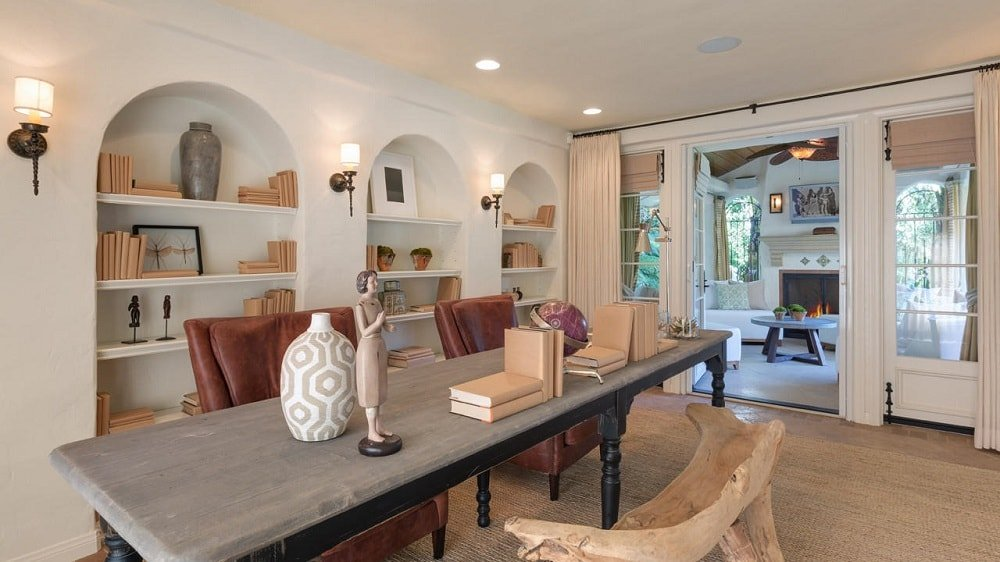 This other view of the home office shows the embedded bookshelves behind the two cushioned chairs. These are then complemented by the warm light of the sconces in between them. Image courtesy of Toptenrealestatedeals.com.