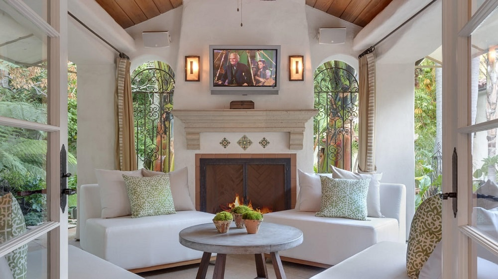The covered patio has a tall cathedral ceiling above the white cushioned chairs that are warmed by the large stone beige fireplace with a wall-mounted TV above it. Image courtesy of Toptenrealestatedeals.com.