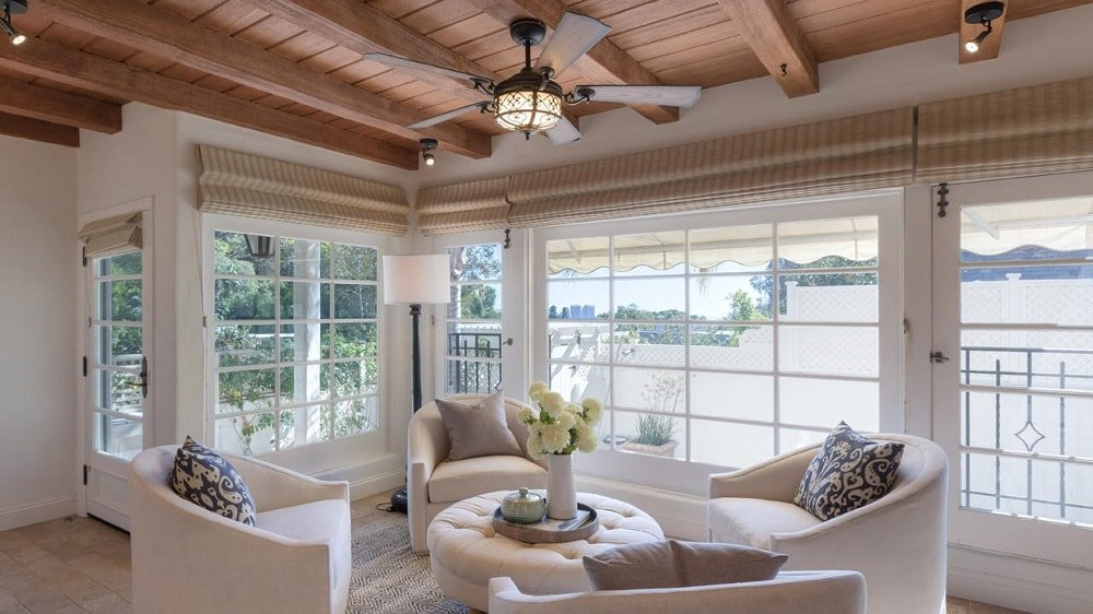 The sunroom of the house has beige cushioned armchairs that surround a beige tufted ottoman. These are then brightened by the glass walls and topped with a wooden ceiling that has exposed beams. Image courtesy of Toptenrealestatedeals.com.