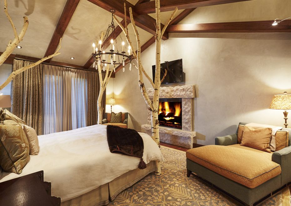 The bedroom has a four-poster bed with rustic posts reaching up to the wooden cathedral ceiling with exposed beams. Across the bed is a stone fireplace topped with a wall-mounted TV. Image courtesy of Toptenrealestatedeals.com.