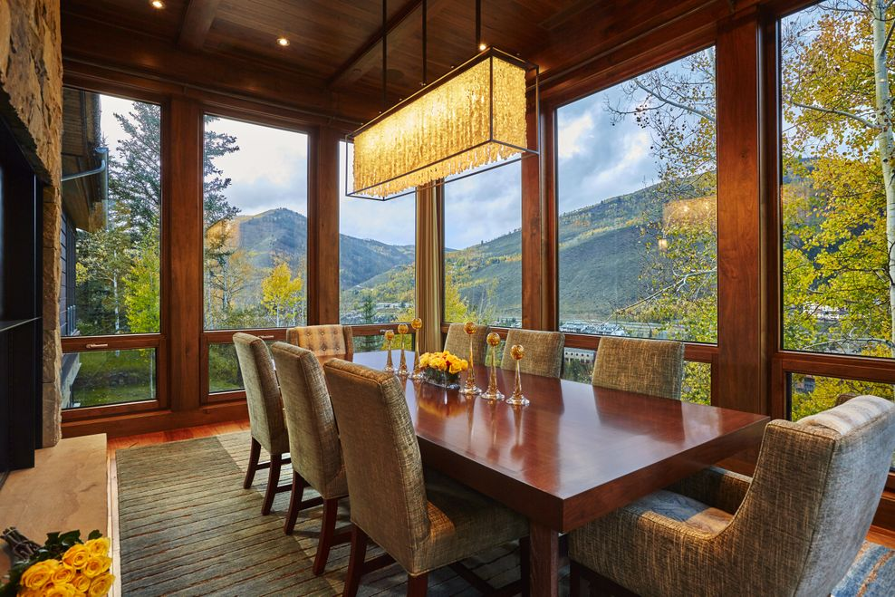 This is the dining room that has a wooden dining table topped with a long and narrow lighting and has glass walls that show the surrounding landscape. Image courtesy of Toptenrealestatedeals.com.
