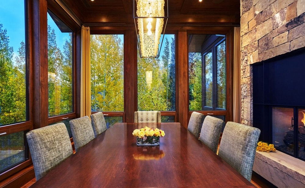 This other view of the dining room showcases the large rectangular wooden dining table that matches perfectly with the wooden frames of the surrounding glass walls and the ceiling. Image courtesy of Toptenrealestatedeals.com.