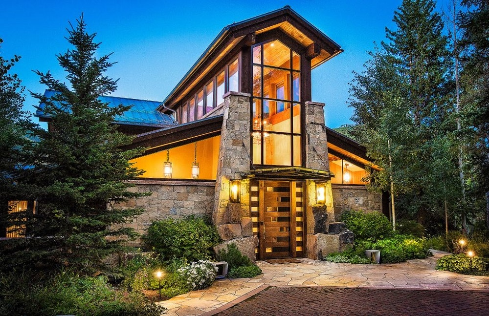 This is the front view of the house. Here you can see the glass walls and transom windows above the foyer and the stone mosaic exterior walls that are adorned with landscaping of shrubs and trees. Image courtesy of Toptenrealestatedeals.com.