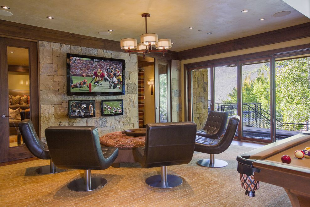 This is the game room that has cushioned leather swivel chairs facing a large cushioned ottoman across from the stone wall that has the wall-mounted TV. Image courtesy of Toptenrealestatedeals.com.