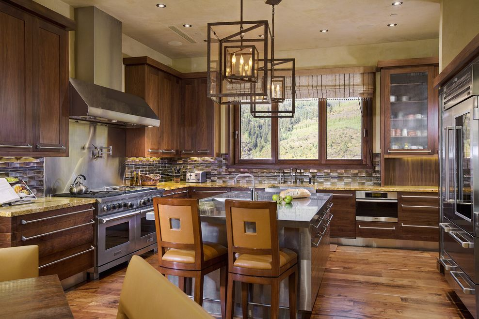 This kitchen has a kitchen island topped with geometric pendant lights that stand out against the light beige ceiling. Across from the island is the cooking area with a stainless steel oven. Image courtesy of Toptenrealestatedeals.com.