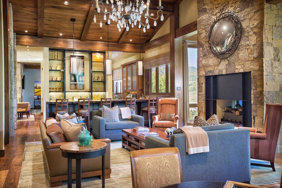 The large living room has a tall wooden cathedral ceiling that hangs a large chandelier over the wooden coffee table across from the large stone fireplace. Image courtesy of Toptenrealestatedeals.com.