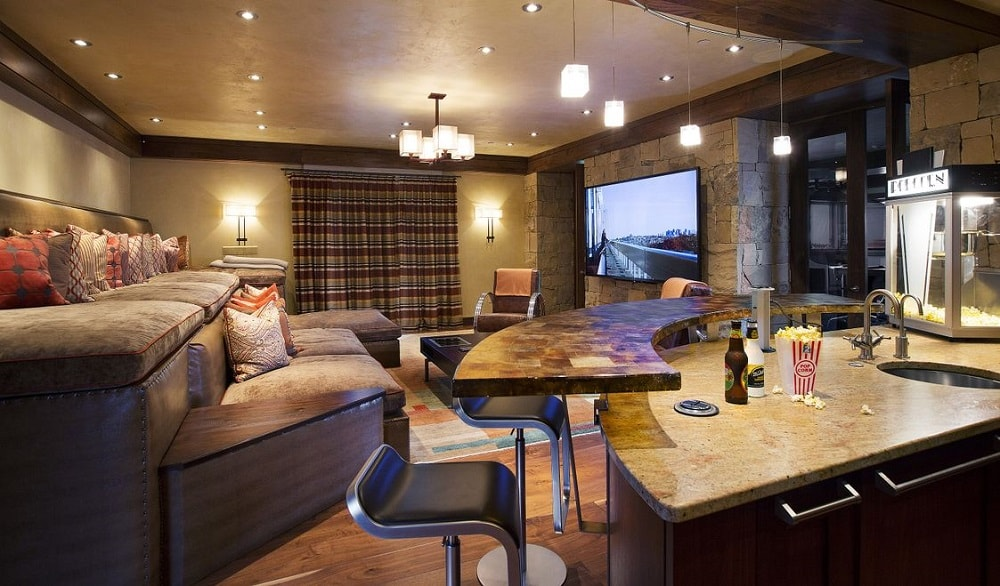 This is the media room of the house with elevated levels of built-in cushioned benches facing the large screen. On the side of this is a small bar paired with modern stools. Image courtesy of Toptenrealestatedeals.com.