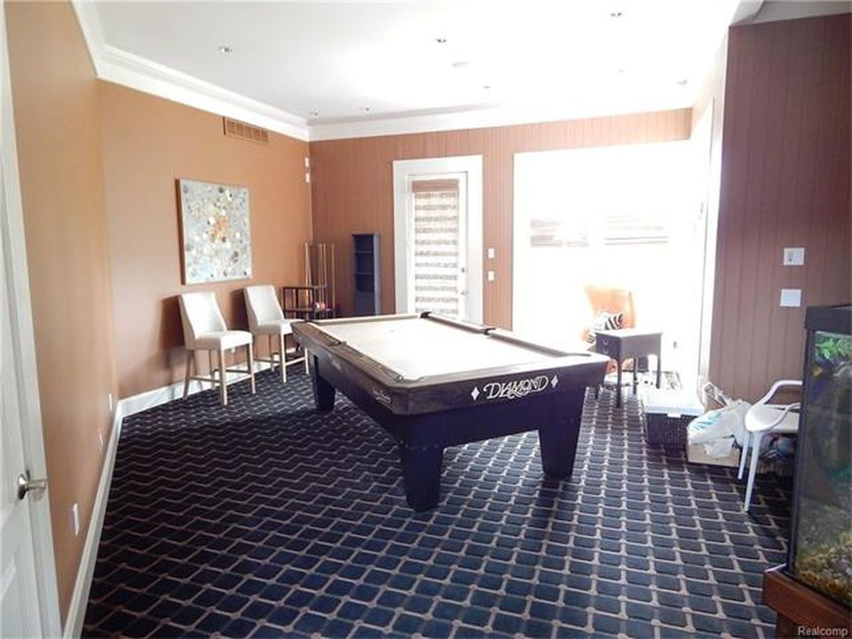A game room featuring brown walls and carpeted flooring. There's a billiards table set as well. Images courtesy of Toptenrealestatedeals.com.