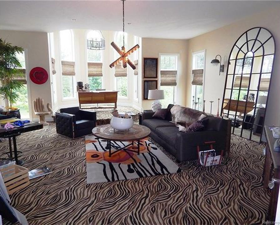 Another living room featuring a black sofa set with a center table. The room features carpeted flooring. Images courtesy of Toptenrealestatedeals.com.