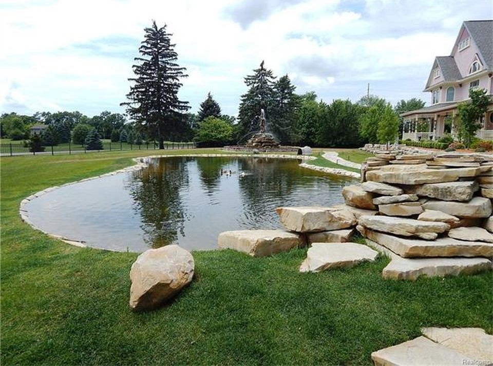 There's also a pond located on the home's lawn area near the statue and fountain landscape design. Images courtesy of Toptenrealestatedeals.com.