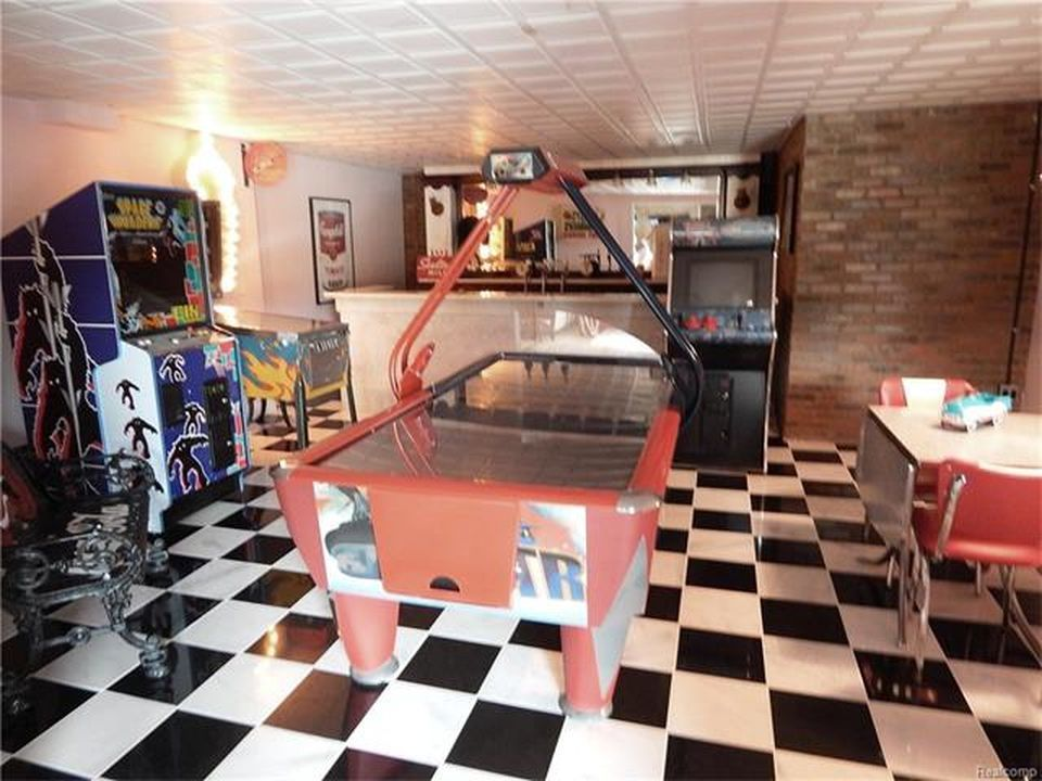 Another look at the home's game room with lots of arcade games and a bar area. Images courtesy of Toptenrealestatedeals.com.