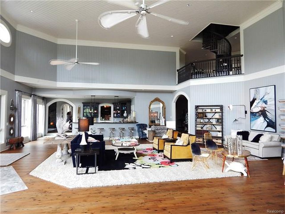 This living space boasts elegant pieces of furniture and an area rug covering the hardwood flooring. Images courtesy of Toptenrealestatedeals.com.