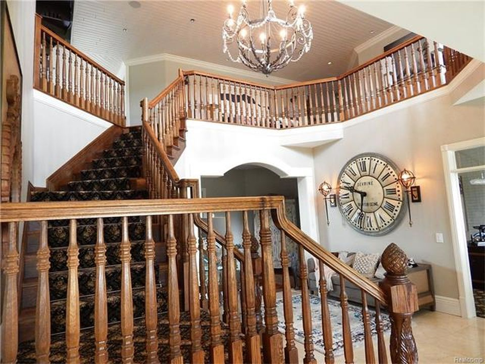 Closer look at the home's wooden staircase with wooden railings and handrails along with carpeted steps. Images courtesy of Toptenrealestatedeals.com.