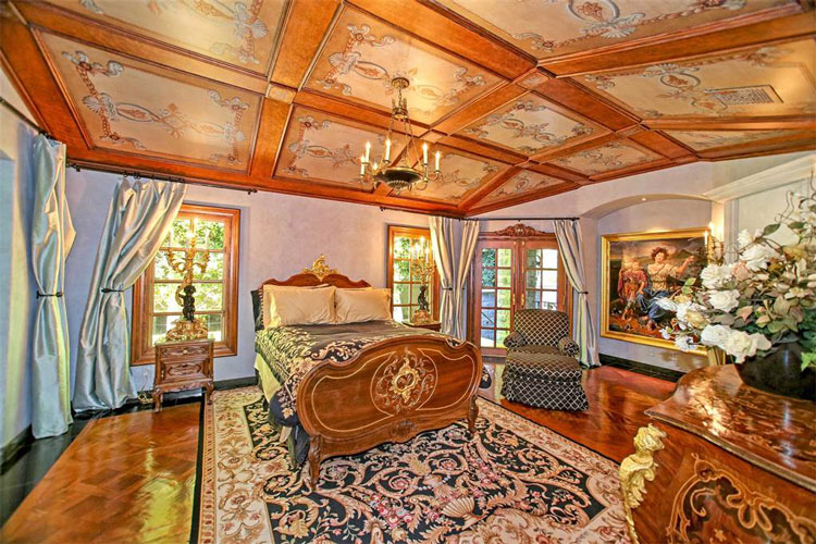 The primary bedroom has a wooden sleigh bed with sheets that match the patterned area rug on the hardwood flooring. This matches perfectly with the wooden accents of the ceiling and the window frames. Image courtesy of Toptenrealestatedeals.com.