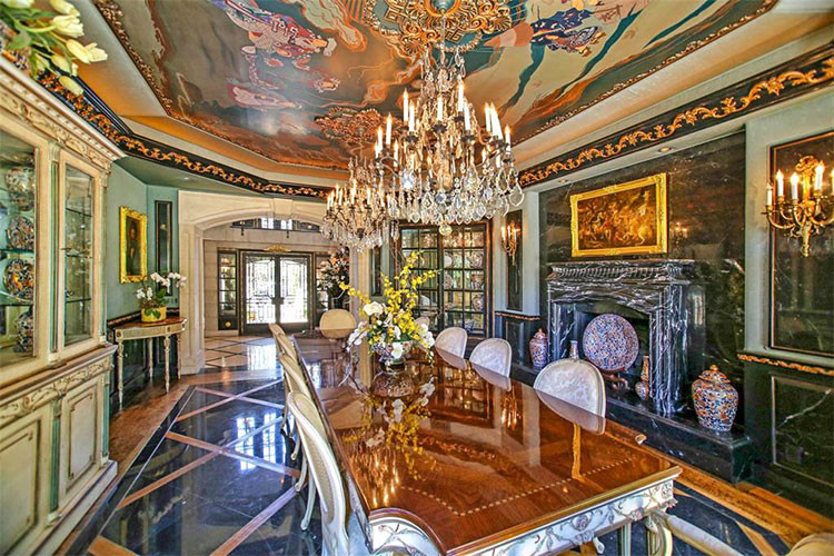 The formal dining room also has a checkered pattern to its black tiles on the floor that makes the large elegant dining table stand out. This is topped with a chandelier that hangs from a tray ceiling filled with colorful murals. Image courtesy of Toptenrealestatedeals.com.