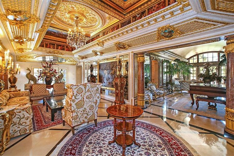 This is the living room with an intricate ceiling of coffers and a circular beige dome in the middle hanging a chandelier over the cushioned sofa set. Image courtesy of Toptenrealestatedeals.com.