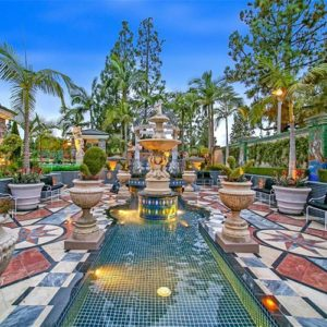 This is the view of the pool surrounded by patterned tiles on its walkways adorned with pedestal planters and a large fountain in the middle. These are then balanced by the tall trees in the background. Image courtesy of Toptenrealestatedeals.com.