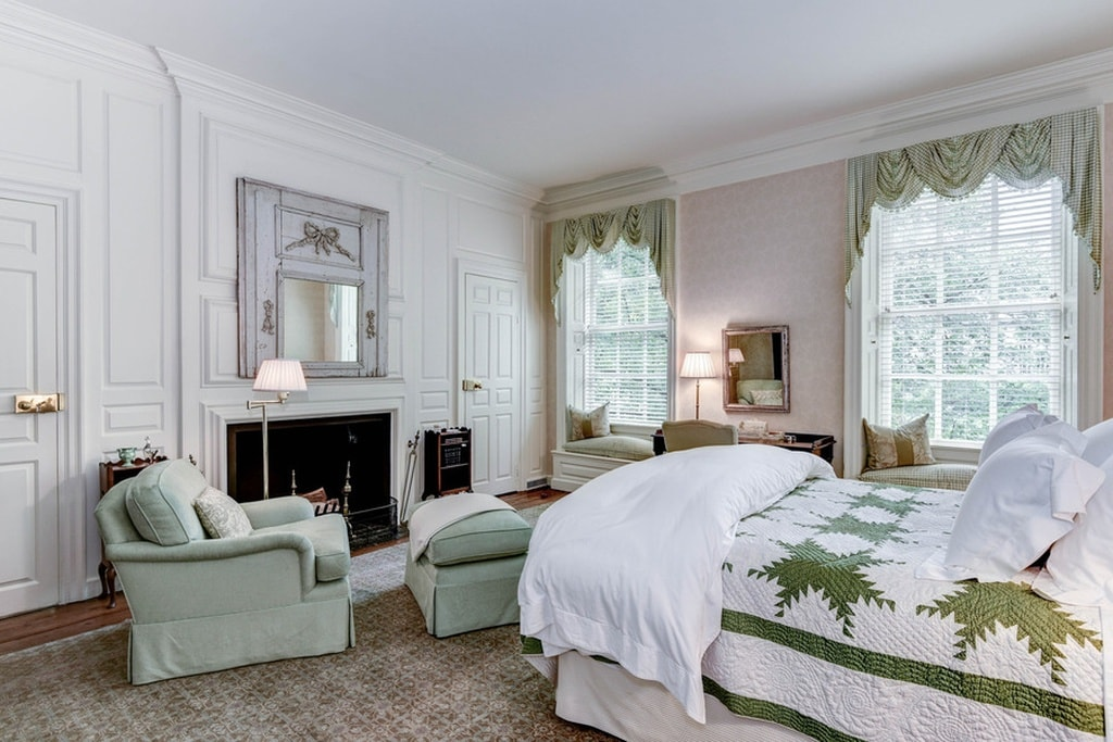 This bedroom has a large fireplace with a white mantle to bring warmth to the cushioned armchair at the foot of the bed. The green patterns on the sheets match the tone of the armchair and the curtains on the far side. Image courtesy of Toptenrealestatedeals.com.