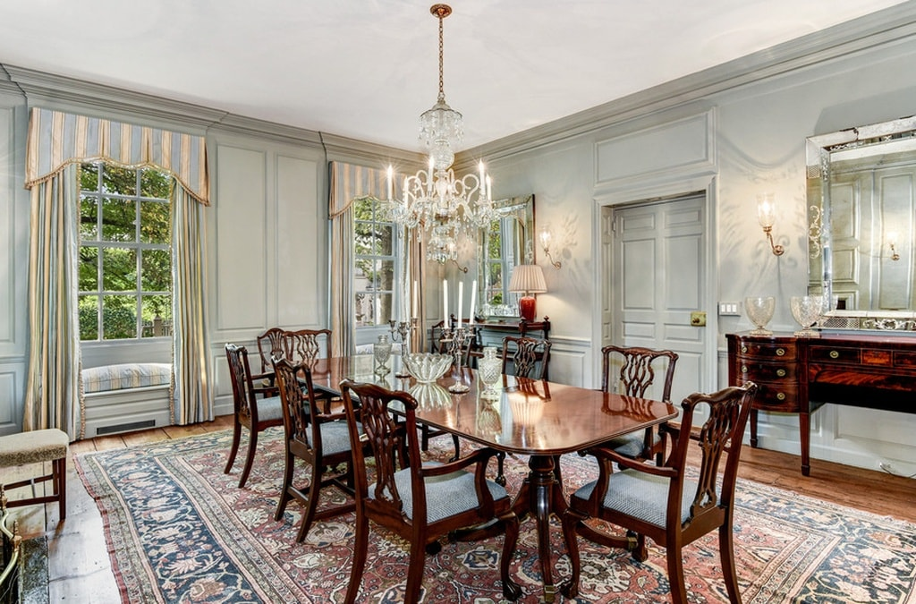 The formal dining room has a large dark wooden table paired with matching wooden chairs. They are complemented by the colorful patterned area rug of the floor and the chandelier hanging from the ceiling. Image courtesy of Toptenrealestatedeals.com.
