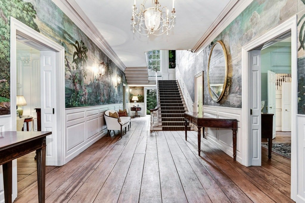 The foyer of the house has dark hardwood flooring to contrast the white wainscoting. These are then complemented by the colorful scenic wallpaper adorned with wall lamps and mirrors. Image courtesy of Toptenrealestatedeals.com.