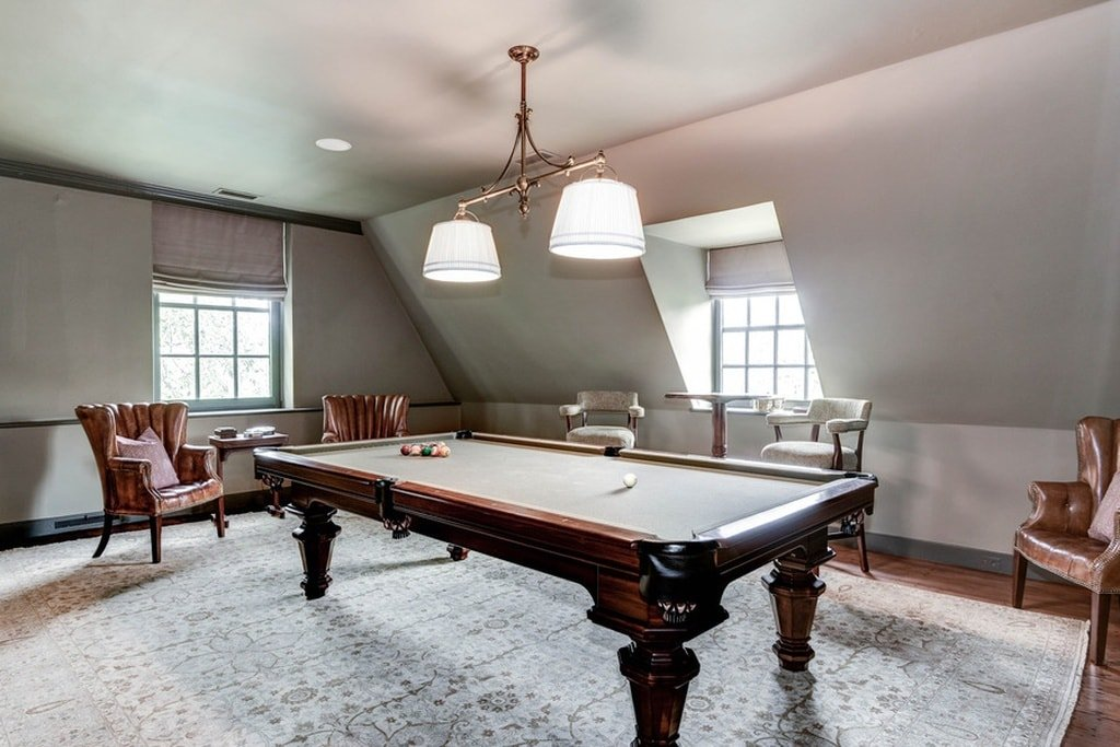The game room at the upper floor of the house has a large wooden pool table illuminated by the natural lights of the windows as well as the decorative lighting of the ceiling. Image courtesy of Toptenrealestatedeals.com.
