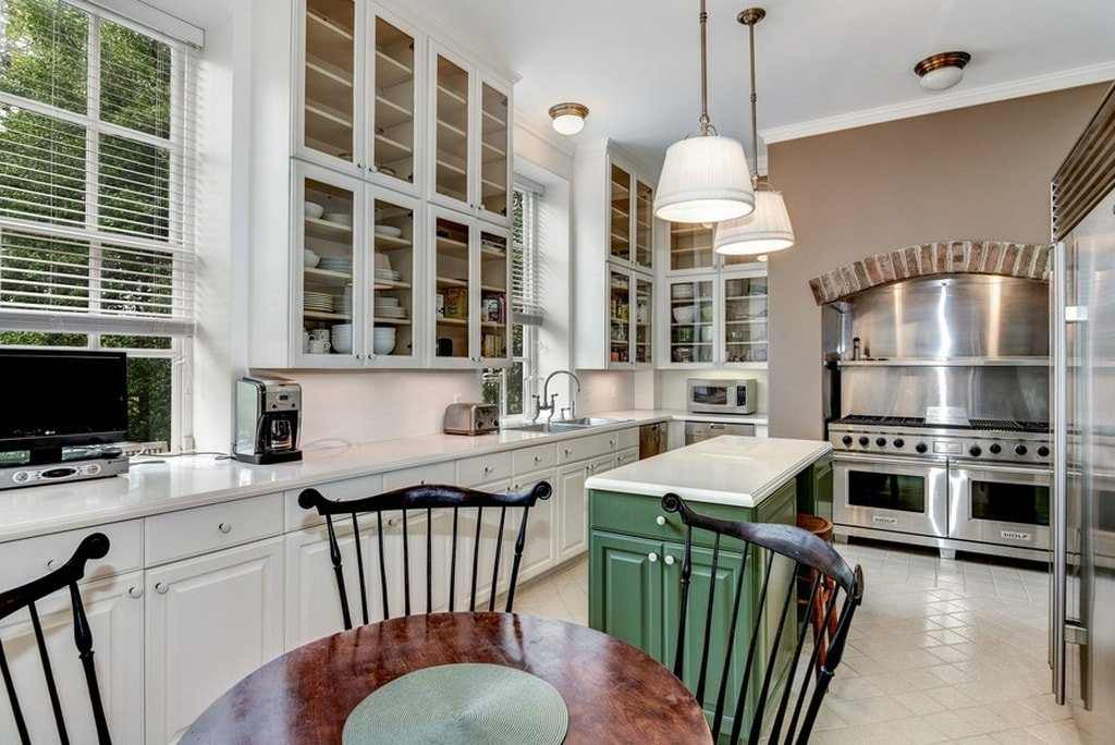 This is one of the kitchens of the house. It has its own dining area of a round wooden table and chairs that stand out against the light tone of the surrounding cabinetry and tall ceiling. Image courtesy of Toptenrealestatedeals.com.