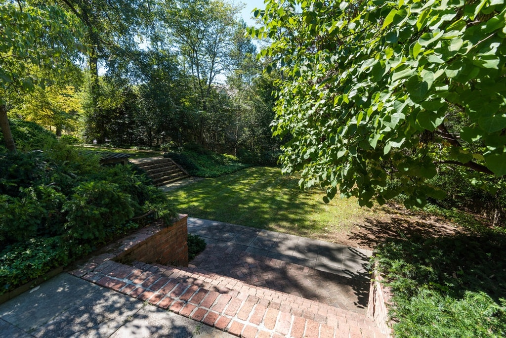 This is a view of the backyard of the house with a spacious lawn filled with mature trees that bring shade and beauty to the area. Image courtesy of Toptenrealestatedeals.com.