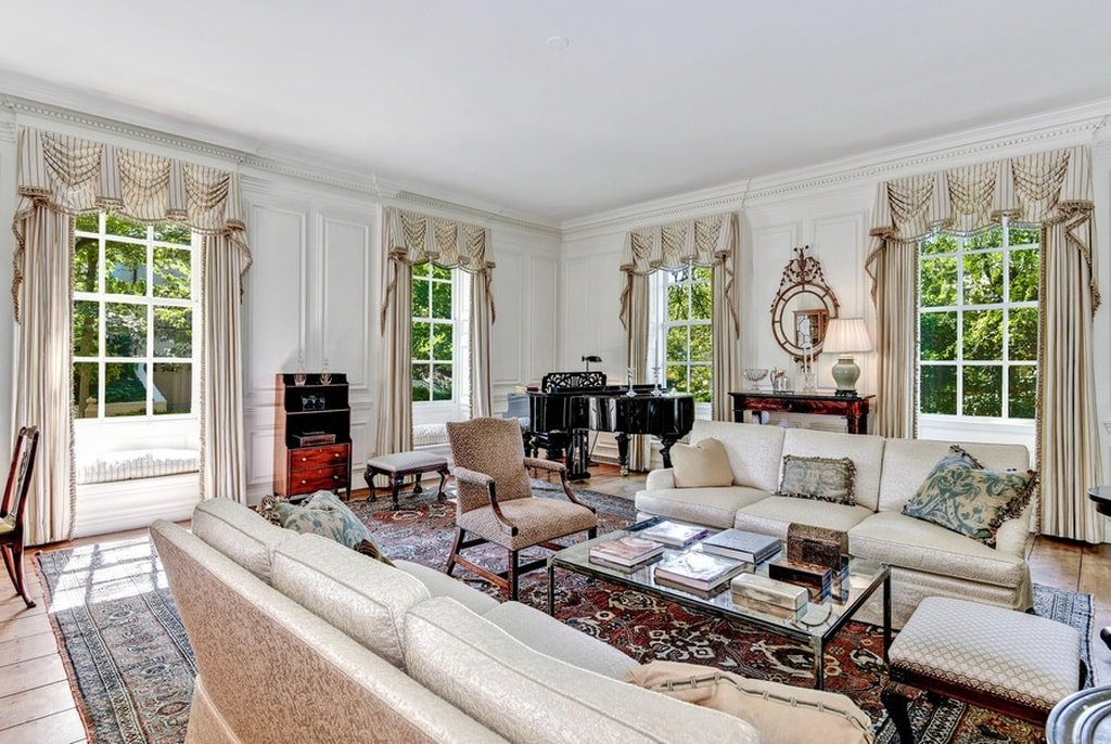 The living room has bright white walls, ceiling and light beige sofas to contrast the colorful patterned area rug. You can also see the fireplace and the grand piano on the corner standing out against the walls. Image courtesy of Toptenrealestatedeals.com.