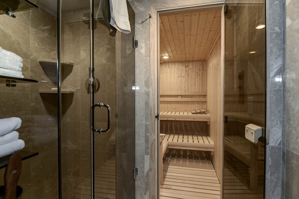 This is the spa with glass-enclosed shower areas and a steam room that has wooden surfaces on its walls, floor, ceiling and the built-in benches. Image courtesy of Toptenrealestatedeals.com.