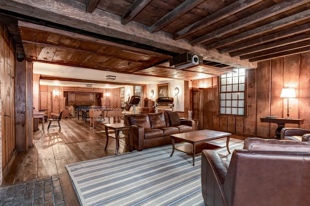 This is the tarn room with a spacious hardwood flooring to match the wooden ceiling with exposed beams. These also match the brown leather sofas and the wooden coffee table on a striped area rug. on the far end, you can see some table games for pastime. Image courtesy of Toptenrealestatedeals.com.