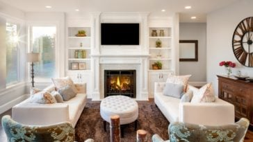 This family room has a consistent white tone to its ceiling and walls that has built-in shelves and cabinets flanking the fireplace with a white mantle.