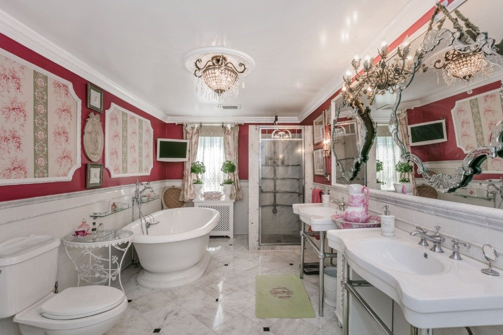 The home has a bathroom with gorgeous red walls and tiles flooring offering a freestanding tub, a walk-in shower and two sinks. Image courtesy of Toptenrealestatedeals.com.