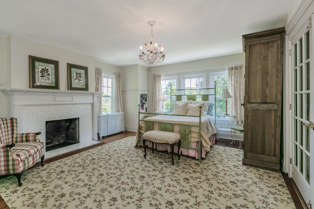 Spacious bedroom with a fireplace on the side. The room has a large area rug and a small chandelier. Image courtesy of Toptenrealestatedeals.com.