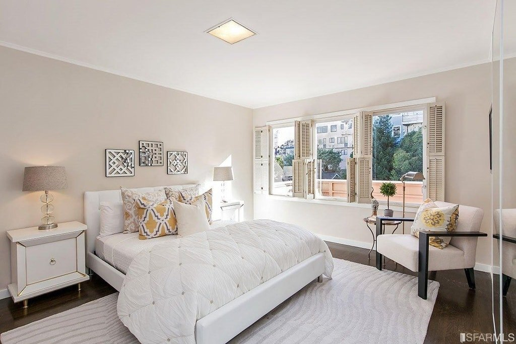 This other bedroom has bright tones on its bed that matches well with the light beige walls and ceiling contrasted by the dark hardwood flooring. Image courtesy of Toptenrealestatedeals.com.