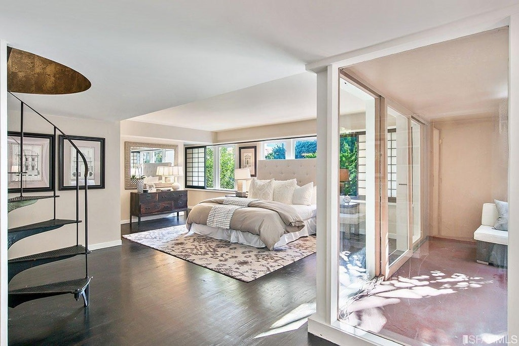 This primary bedroom has a spacious hardwood flooring that matches the wooden console table beside the bed that has a large beige cushioned headboard against the row of windows. Image courtesy of Toptenrealestatedeals.com.