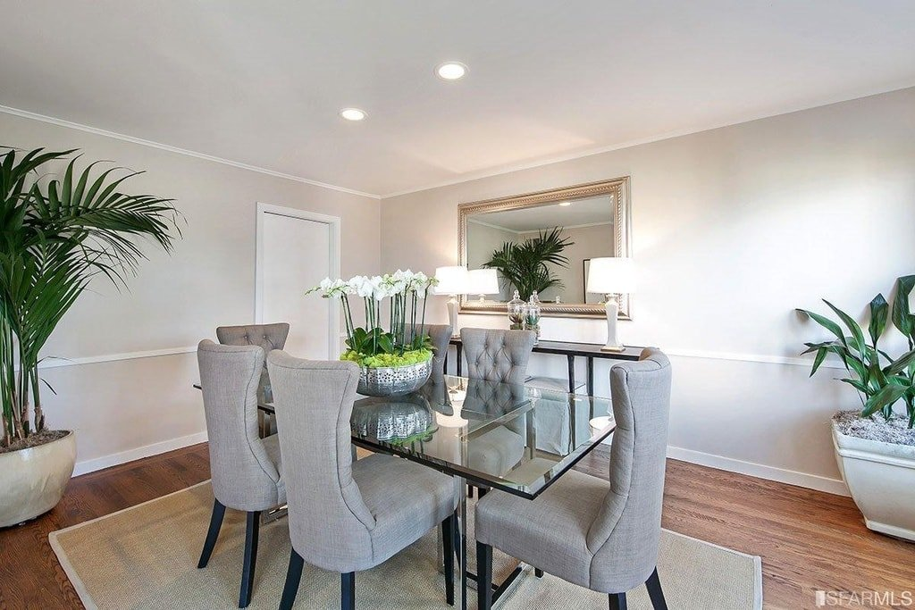 This is the formal dining room that has a glass-top dining table surrounded by gray upholstered chairs. On the side is a console table topped with table lamps and a wall-mounted mirror. Image courtesy of Toptenrealestatedeals.com.