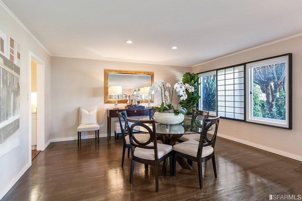 This is the other formal dining room with a round glass-top dining table surrounded by dark wooden chairs that match the dark hardwood flooring and the frames of the windows. Image courtesy of Toptenrealestatedeals.com.