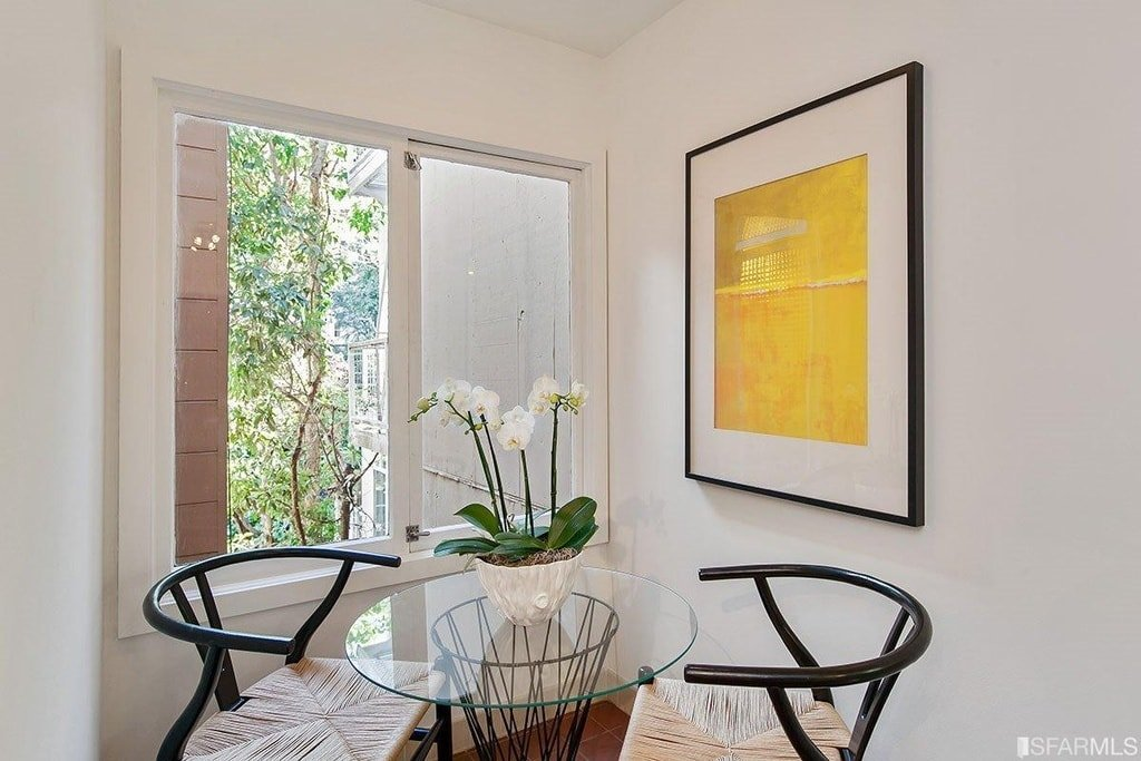 This is a breakfast nook with a small round glass-top table paired with a couple of wishbone chairs beside a window. Image courtesy of Toptenrealestatedeals.com.