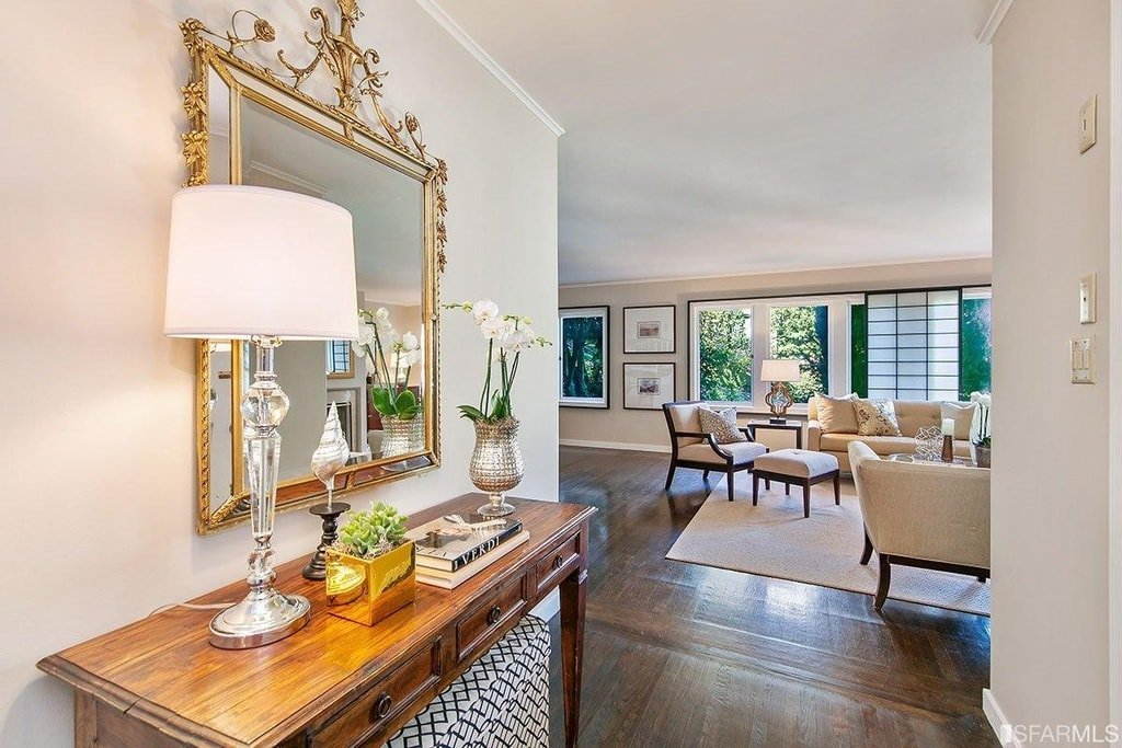 The foyer has a wooden console table on the side topped with a table lamp and a wall-mounted mirror with intricate gold frames to contrast the light beige wall. Image courtesy of Toptenrealestatedeals.com.