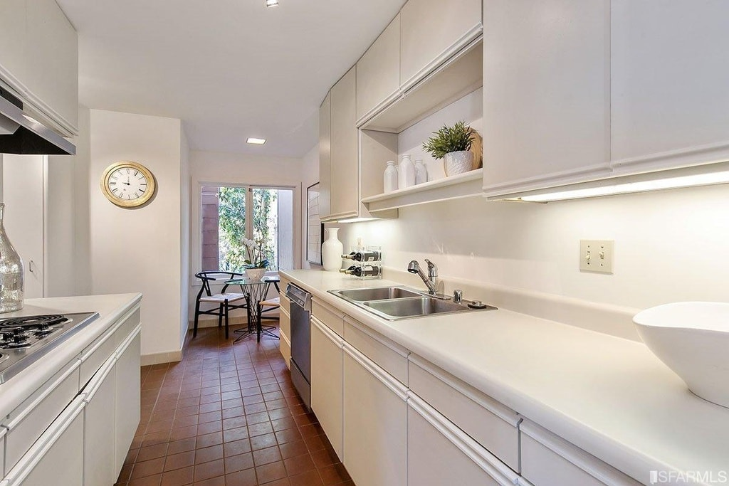 The long and narrow galley-style kitchen has terracotta flooring tiles that contrast the light beige tone of the cabinetry, walls and the ceiling. Image courtesy of Toptenrealestatedeals.com.