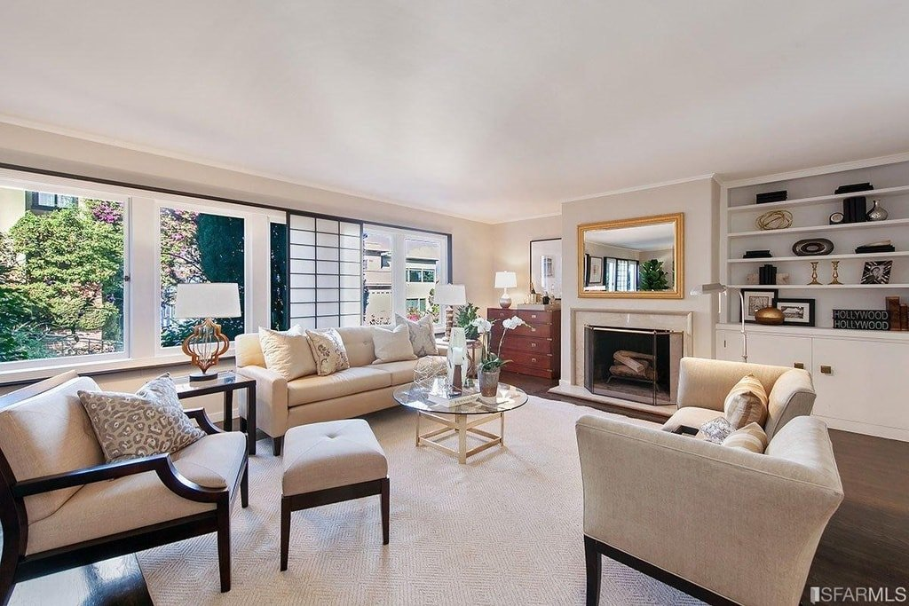 This is the living room that has consistent beige tones on its ceiling, area rug and walls with a fireplace topped by a wall-mounted mirror across from the beige sofa set and glass-top coffee table. Image courtesy of Toptenrealestatedeals.com.