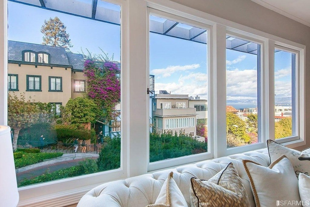 This is the row of glass windows above the tifted white sofa that brings in natural light as well as provide a picturesque background for the room. Image courtesy of Toptenrealestatedeals.com.
