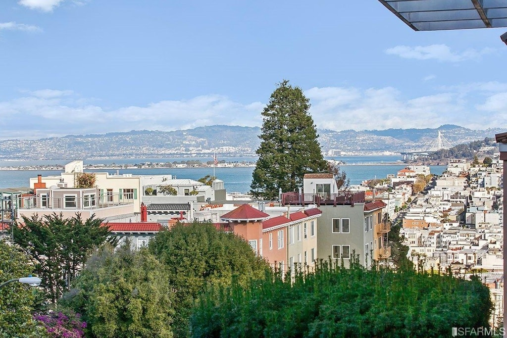This is a look at the view afforded by the second floor balcony. It gives us a sweeping scenery of houses, tall trees and the bay in the far distance. Image courtesy of Toptenrealestatedeals.com.