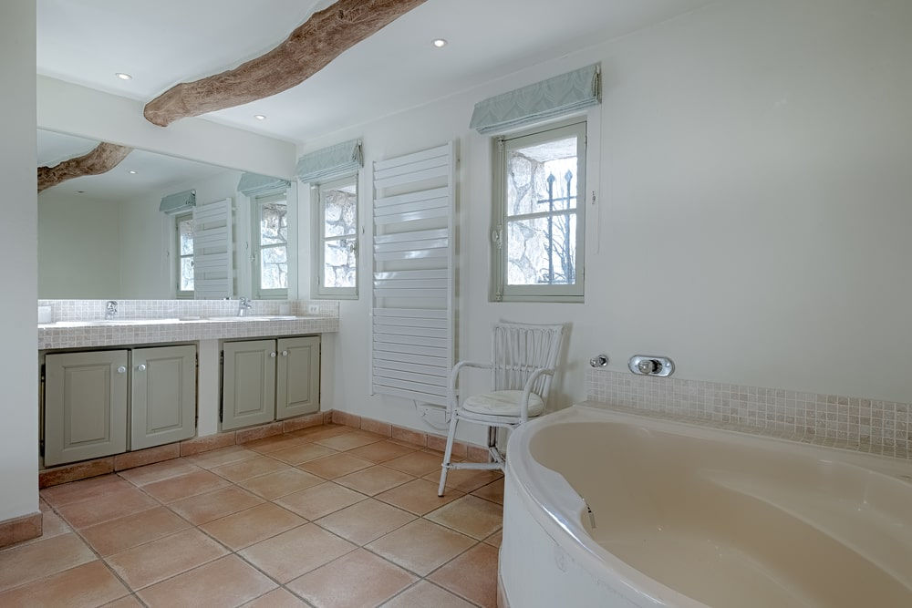 This bathroom has a corner bathtub across from the vanity on the far side that has cabinets and a large mirror. You can also see here the single exposed wooden log beam of the ceiling. Image courtesy of Toptenrealestatedeals.com.