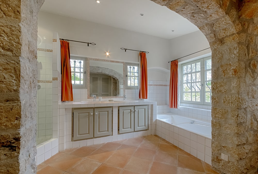 This bathroom has a bathtub on the side underneath the widow. Next to this is the vanity topped with a mirror that is flanked by windows. Image courtesy of Toptenrealestatedeals.com.