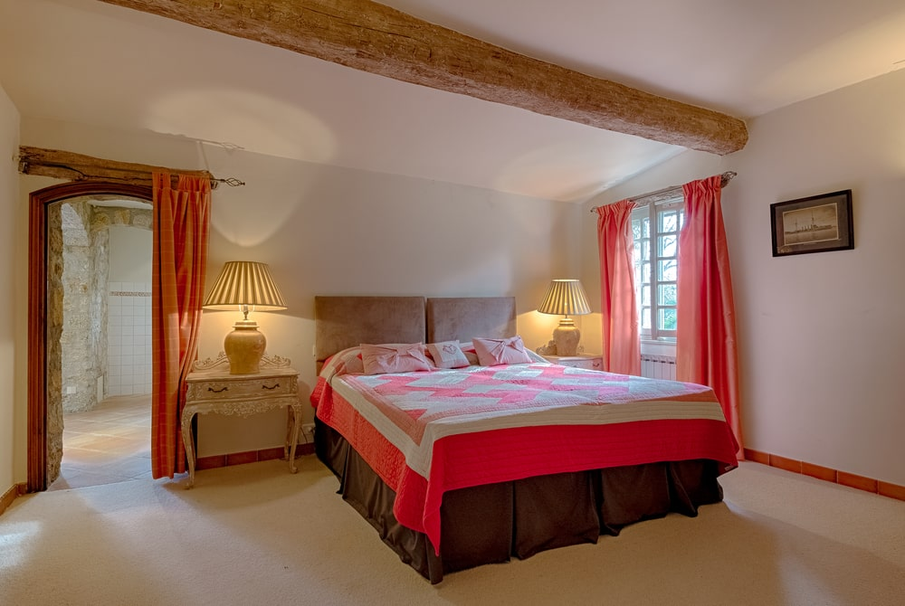 This other bedroom has vibrant red curtains that match the sheets of the bed and the molding. You can also see here the single large wooden log beam of the ceiling. Image courtesy of Toptenrealestatedeals.com.